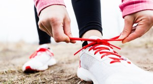Woman runner tying sport shoes. Walking or running legs autumn adventure and exercising outdoors.